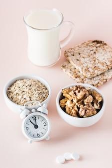 Durma bem. alimentos para uma boa noite de sono - leite, nozes, pão estaladiço, aveia e despertador em fundo rosa. visão vertical