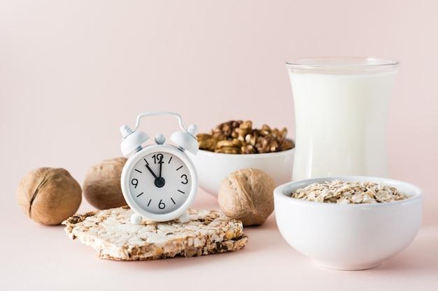 Durma bem. relógio despertador no fundo de produtos para um bom adormecimento - leite, nozes, pão crocante de aveia em um fundo rosa