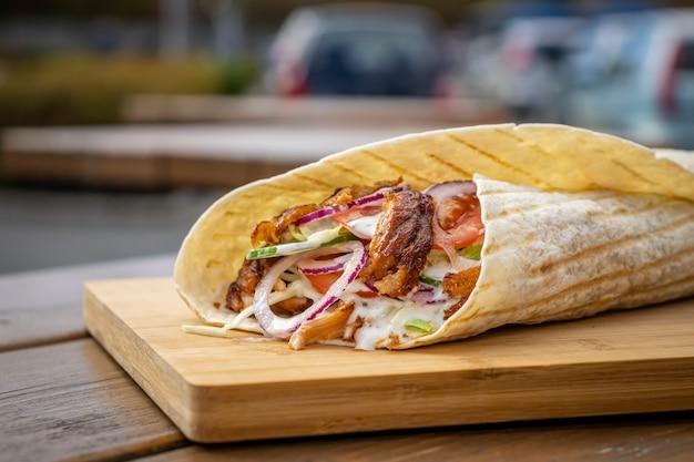 Durum kebab em uma barraca de comida de rua local em uma tábua de madeira
