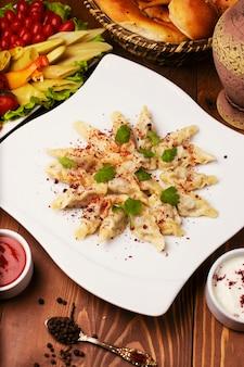Dushbere de comida tradicional caucasiana, gurze servido com iogurte e molho de tomate. em chapa branca decorada com turshu na mesa de madeira