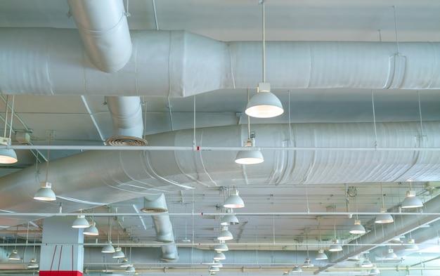 Duto de ar, tubo de ar condicionado, tubo de fiação e sistema de extinção de incêndios. fluxo de ar e sistema de ventilação. interior do edifício. lâmpada do teto com luz aberta.