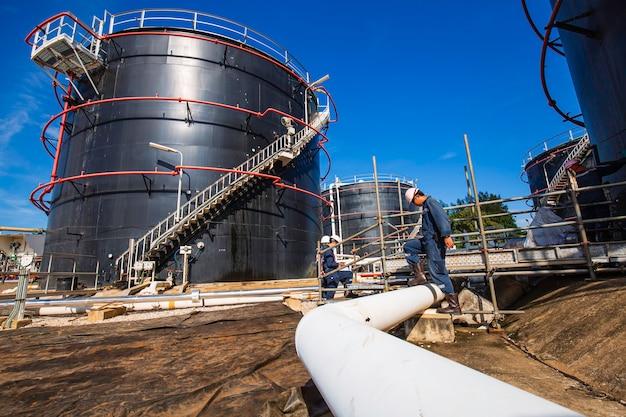 Duto visual de inspeção de trabalhador masculino e petróleo bruto do tanque de armazenamento