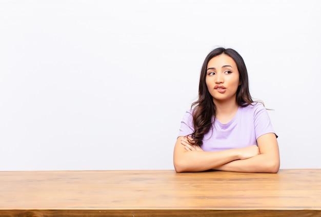 Duvidar ou pensar, morder o lábio e sentir-se inseguro e nervoso, olhando para copiar espaço ao lado