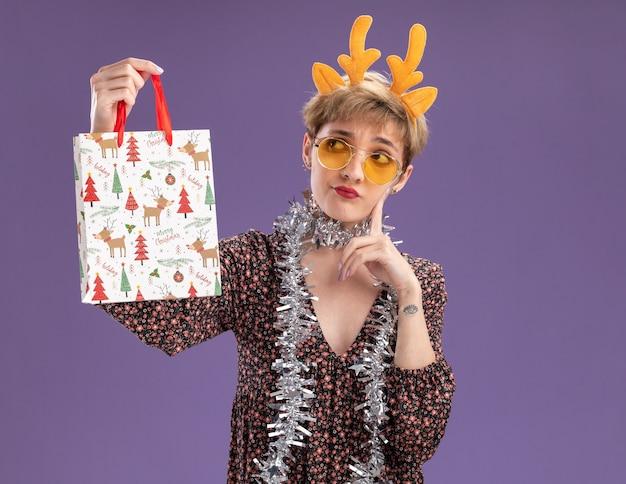Duvidosa jovem bonita usando uma faixa de chifres de rena e uma guirlanda de ouropel em volta do pescoço com óculos segurando uma sacola de presente de natal olhando para ela tocando o rosto isolado na parede roxa com espaço de cópia