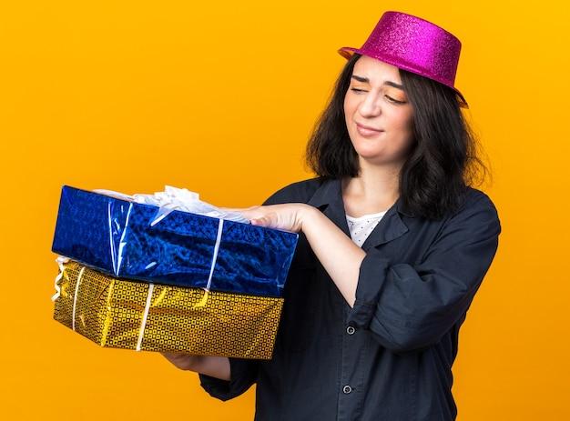 Duvidosa jovem caucasiana festeira com chapéu de festa segurando e olhando para pacotes de presentes isolados na parede laranja
