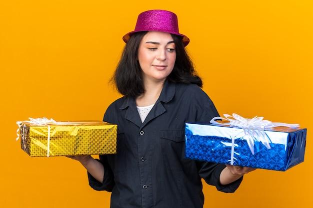 Duvidosa jovem caucasiana festeira com chapéu de festa segurando pacotes de presentes, olhando para um deles isolado na parede laranja