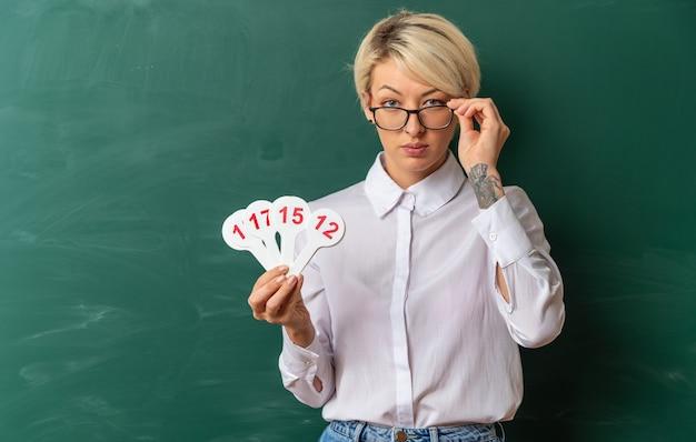 Duvidosa jovem loira professora usando óculos em uma sala de aula em frente ao quadro-negro mostrando número de fãs segurando os óculos olhando para frente com espaço de cópia