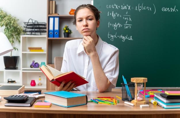 Duvidosa jovem professora de matemática sentada na mesa com o material escolar segurando o livro, mantendo a mão sob o queixo, olhando para frente na sala de aula
