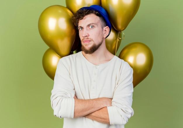 Duvidoso jovem bonito eslavo festeiro usando chapéu de festa em pé com a postura fechada em frente a balões, olhando para frente, isolado na parede verde oliva