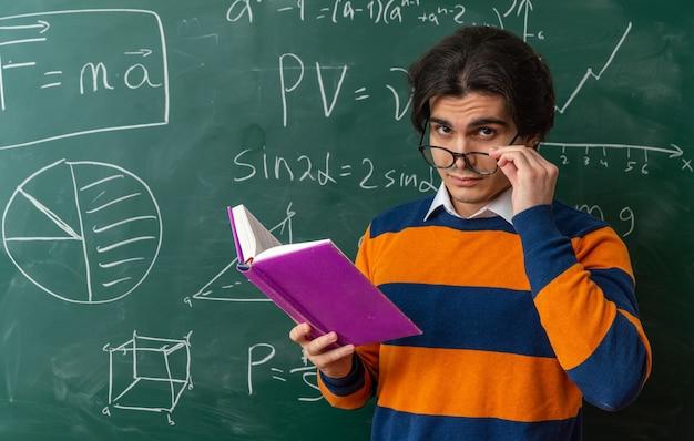 Duvidoso jovem professor de geometria usando óculos em frente ao quadro-negro na sala de aula olhando para frente segurando um livro aberto agarrando os óculos