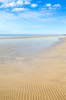 Dzintari beach, jurmala, letônia. areia ondulada na praia, mar e céu azul com nuvens.
