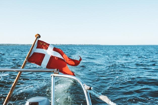 E a bandeira branca em um barco flutuando no topo do oceano sob um céu azul durante o dia