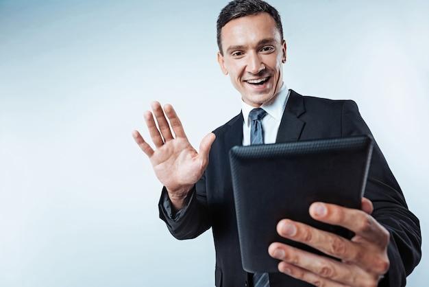 E aí, cara. foto de baixo ângulo de um cara maduro animado vestindo um terno dizendo olá para o amigo enquanto falava com ele durante uma videochamada em um computador tablet.
