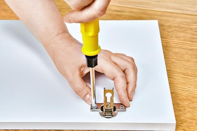 É apertado nas dobradiças das portas dos móveis com chave de fenda no montador de móveis.