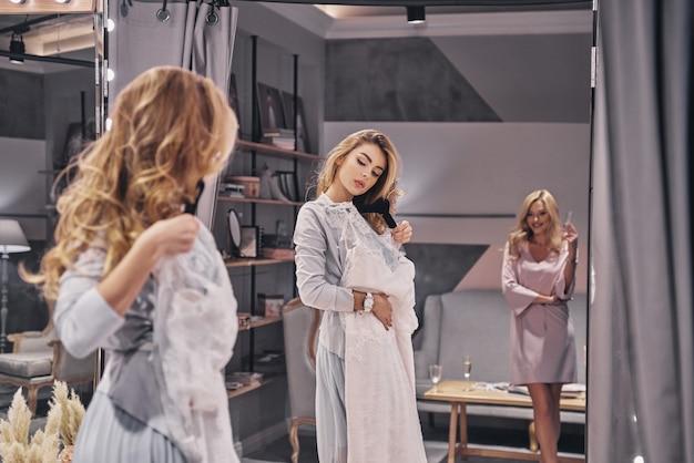 É bom o suficiente? mulheres jovens e atraentes experimentando um vestido de noiva enquanto passam um tempo na loja de noivas com a namorada