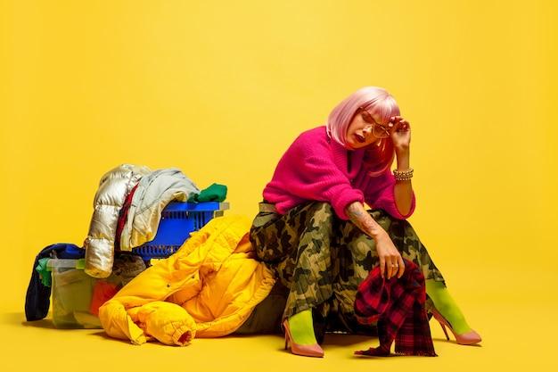 É difícil ser um influenciador. lavanderia mais longa com coleção de roupas. retrato de uma mulher caucasiana em fundo amarelo. linda modelo loira. conceito de emoções humanas, expressão facial, vendas, anúncio.