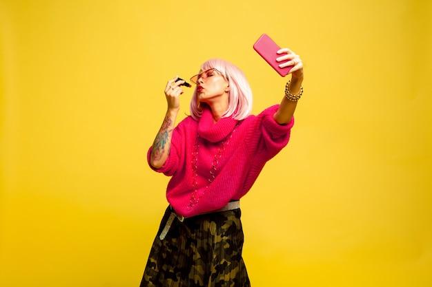 É difícil ser um influenciador. não consigo fazer as pazes sem selfie ou vlog. retrato de uma mulher caucasiana em fundo amarelo. linda modelo loira. conceito de emoções humanas, expressão facial, vendas, anúncio.
