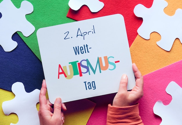 E está segurando uma página com texto em alemão que significa 2 de abril, dia da conscientização mundial do autismo