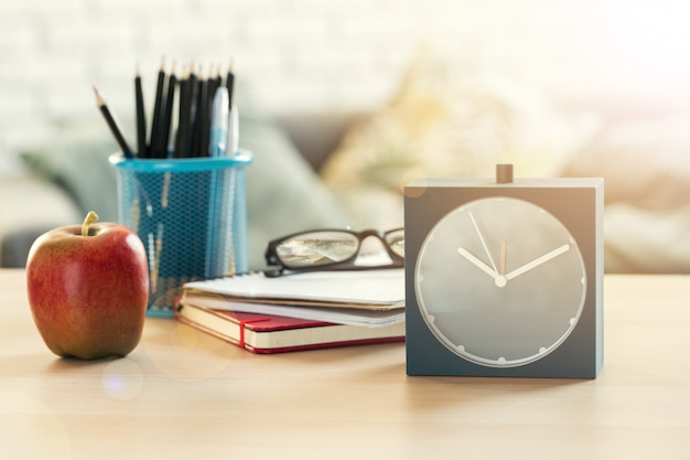 É hora da escola, despertador vintage e maçã na mesa de madeira