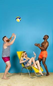É hora de atividade. amigos felizes tomam selfie, jogando vôlei no fundo azul do estúdio. conceito de emoções humanas, expressão facial, férias de verão ou fim de semana. frio, verão, mar, oceano.