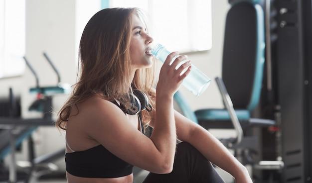 É hora de beber água. foto de uma linda mulher loira na academia no fim de semana