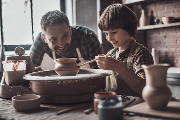 É hora de criar algo ótimo. garotinho desenhando em um pote de cerâmica na aula de cerâmica, enquanto um homem de avental está perto dele