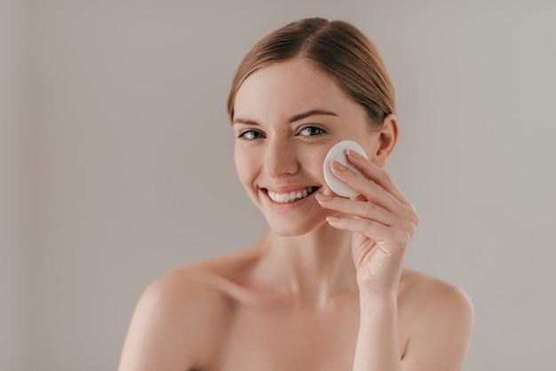 É hora de cuidar da pele. retrato de estúdio de uma mulher atraente limpando a pele com uma almofada de algodão em pé contra o fundo