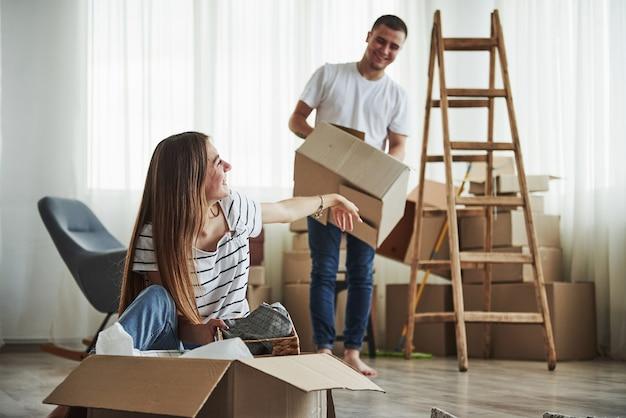 É hora de desempacotar essas caixas. casal jovem alegre em seu novo apartamento. concepção de movimento.
