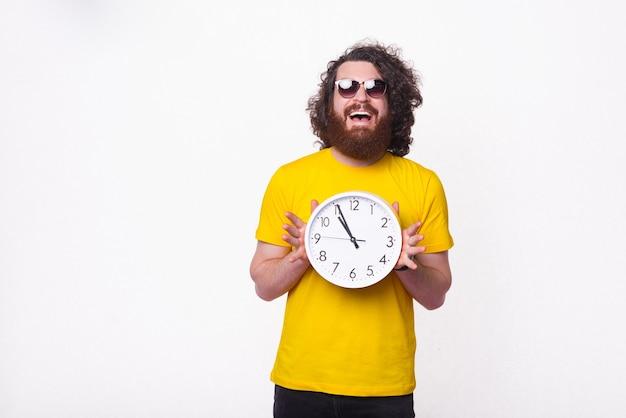 É hora de diversão no verão, diz um jovem barbudo sobre fundo branco.