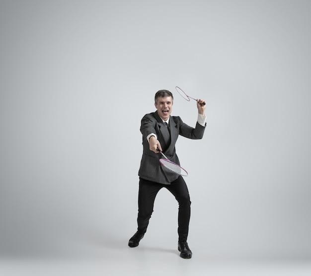 É hora de emoções. homem com roupa de escritório joga badminton com duas raquetes em fundo cinza
