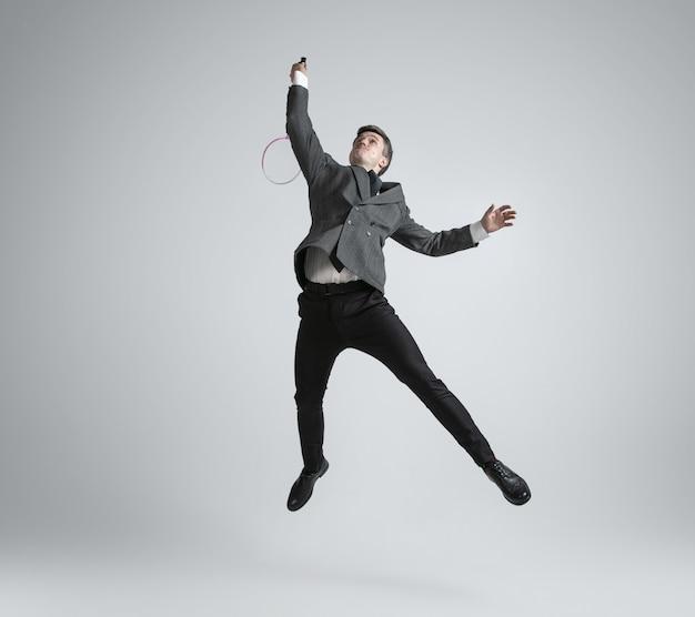 É hora de emoções. homem com roupa de escritório jogando badminton em fundo cinza