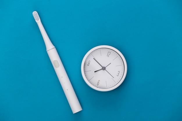 É hora de escovar os dentes. escova de dentes e relógio em azul
