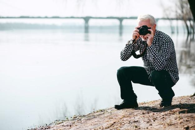 É hora de experimentar. homem maduro criativo sentado e tirando fotos