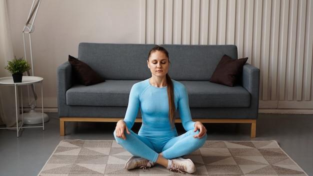 É hora de fazer ioga. mulher jovem e atraente se exercitando e sentada em uma posição de ioga enquanto descansa em casa