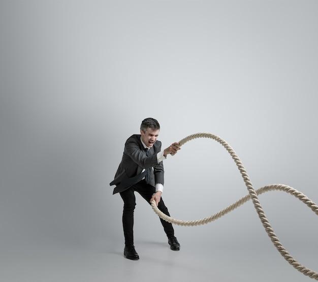 É hora de força. homem com roupa de escritório, treinamento com cordas na parede cinza. obtenha metas, superação de problemas, prazos. empresário em movimento, ação. esporte, estilo de vida saudável, trabalho.