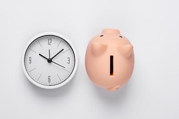 É hora de ganhar dinheiro. depósito. relógio branco e cofrinho em fundo branco. tiro de estúdio minimalista. vista do topo