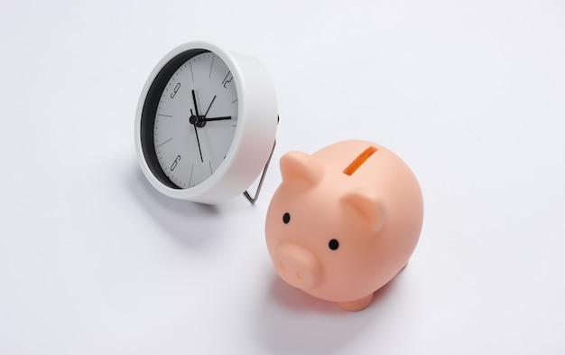É hora de ganhar dinheiro. depósito. relógio branco e cofrinho na superfície branca. tiro de estúdio minimalista.