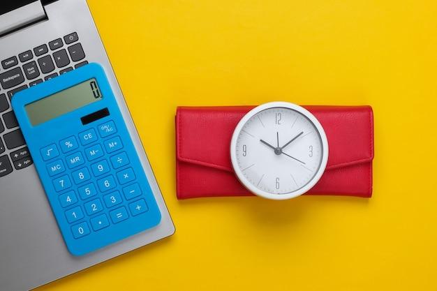 É hora de ganhar dinheiro. negócio online. relógio branco, laptop, calculadora e carteira vermelha na superfície amarela. vista do topo. postura plana