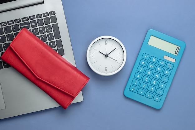 É hora de ganhar dinheiro. negócio online. relógio branco, laptop, calculadora e carteira vermelha sobre fundo roxo. vista do topo. postura plana