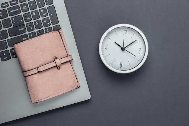 É hora de ganhar dinheiro. negócios online. relógio branco, laptop e carteira na superfície cinza. tiro de estúdio minimalista. vista do topo