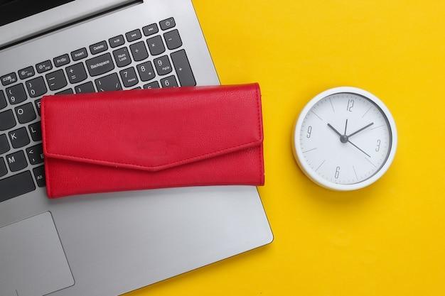 É hora de ganhar dinheiro. negócios online. relógio branco, laptop e carteira vermelha na superfície amarela. tiro de estúdio minimalista. vista do topo