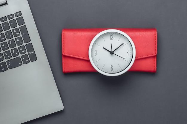 É hora de ganhar dinheiro. negócios online. relógio branco, laptop e carteira vermelha na superfície cinza. tiro de estúdio minimalista. vista do topo