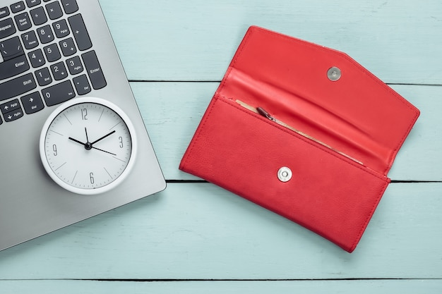 É hora de ganhar dinheiro. negócios online. relógio branco, laptop e carteira vermelha na superfície de madeira azul. tiro de estúdio minimalista. vista do topo