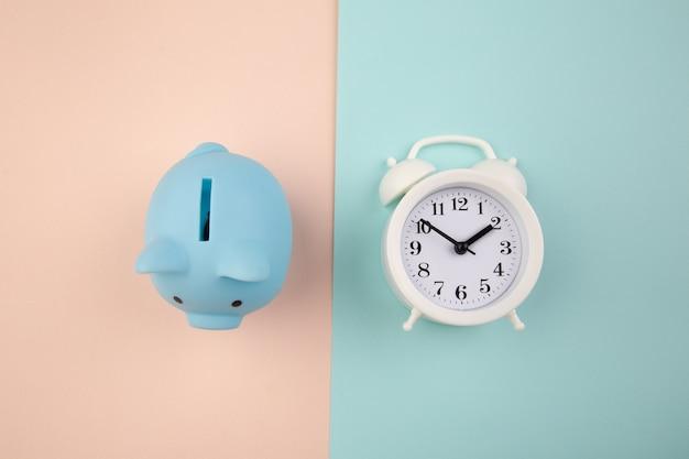 É hora de investir. relógio branco e cofrinho azul sobre fundo rosa pastel azul.