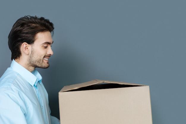 É hora de partir. homem sério bonito e simpático sentado no chão e olhando para a caixa enquanto a abre