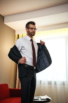 É hora de relaxar após a viagem de negócios. empresário de óculos tira a jaqueta perto do sofá vermelho no quarto do hotel