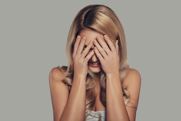 É hora de se esconder. mulher jovem e bonita cobrindo o rosto com as mãos e sorrindo em pé contra um fundo cinza