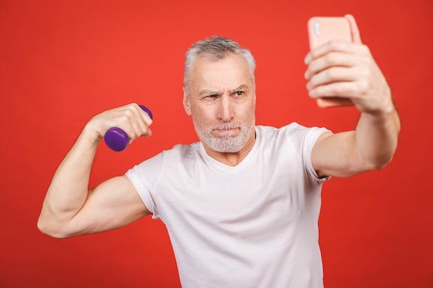 É hora de tirar uma selfie! retrato do close-up de um homem sênior que exercita com halteres. usando o telefone