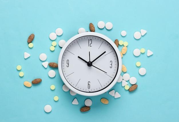 É hora de tomar os comprimidos. relógio branco com comprimidos em fundo azul pastel. vista do topo. postura plana