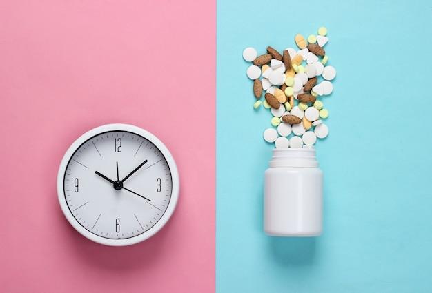 É hora de tomar os comprimidos. relógio branco com frasco de comprimidos em fundo azul-rosa pastel. vista do topo. postura plana